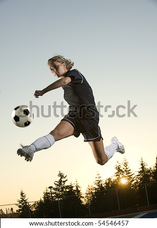 Girl kicks soccer ball in mid air in the early morning. Vertical shot.