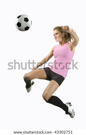 Girl Kicks soccer ball in mid air with a blank white background