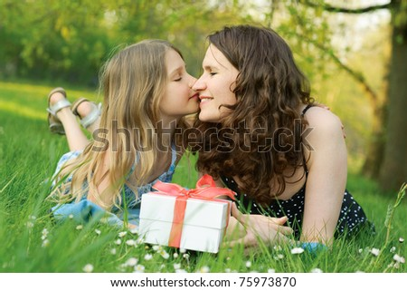 Girl kissing her mother and holding the gift box
