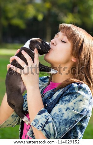 Girl kissing her puppy American Staffordshire Terrier