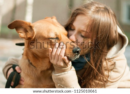 Girl kissing hugging dog pet cute adorable red dog friendly closeup closing eyes funny animals