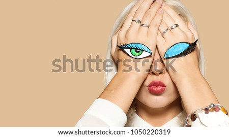 Girl kissing with closed and open eyes painted on her hands. Studio portrait of beautiful blonde model on beige background. Concept of flirting and fun.