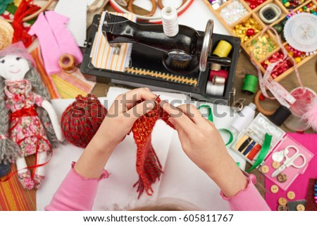 girl knit doll clothes, top view, sewing accessories top view, seamstress workplace, many object for needlework, handmade and handicraft