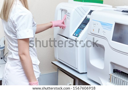 Girl laboratory assistant in a white coat works on an automatic blood test analyzer in a medical laboratory.