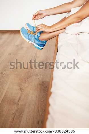 Girl lace her run shoes sitting in bed at the morning #338324336