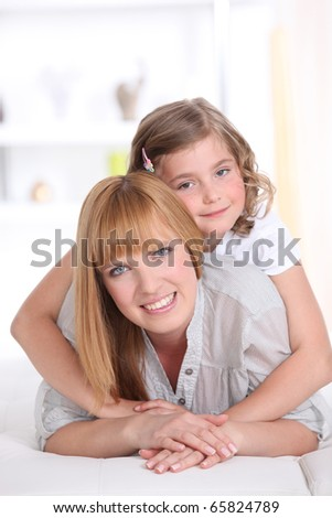 Girl laid on the back of a smiling woman - stock photo