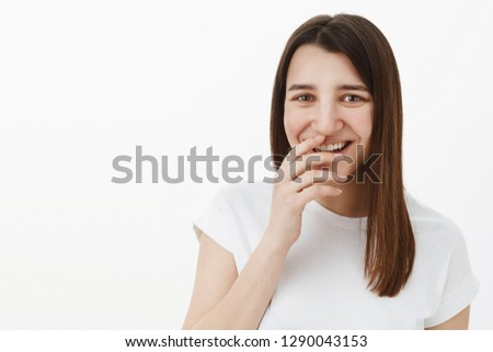 Girl laughing over you as having fun and fooling around being in playful upbeat mood giggling, covering perfect smile with hand and gazing amused at camera posing in white t-shirt against gray wall