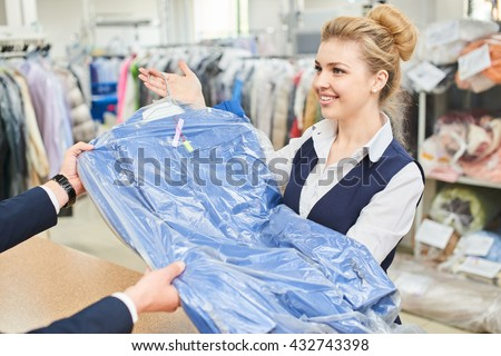Girl Laundry worker pays into the hands of clean clothes at the dry cleaners