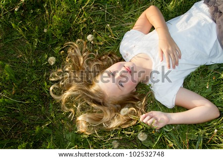 Girl Laying In A Grassy Field With Dandelions Stock Photo ...