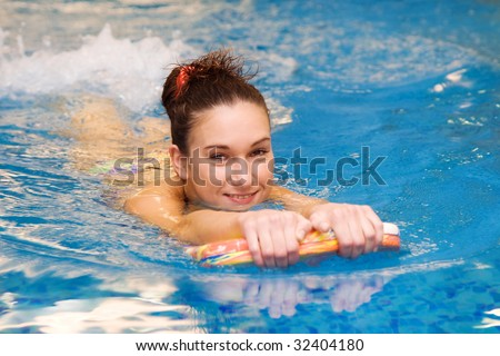 girl learn to swim with board in the swimming pool