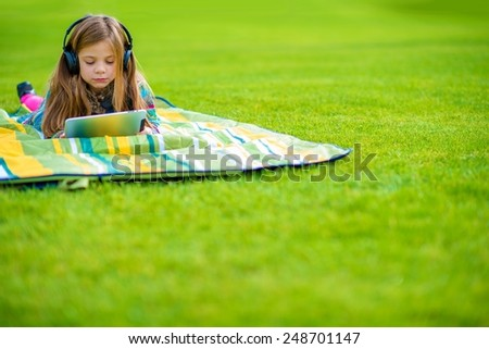 Girl Learning Language While Laying on the Park Green Field. Caucasian Girl with Wireless Headphones and Tablet.