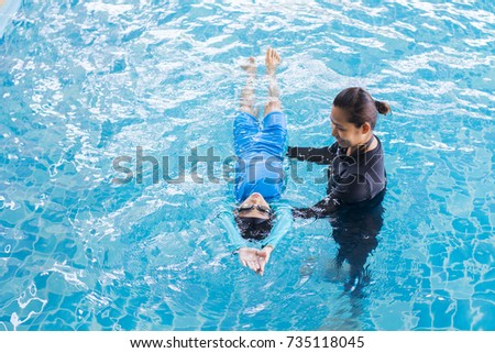 Girl learning to swim with coach at the leisure center #735118045