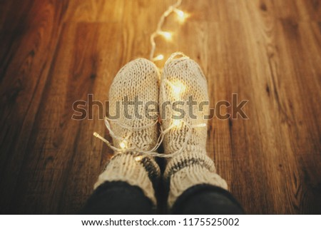 girl legs in stylish warm sock in garland lights on floor with rug in festive room. decor for winter holidays. atmospheric moment. cozy winter days