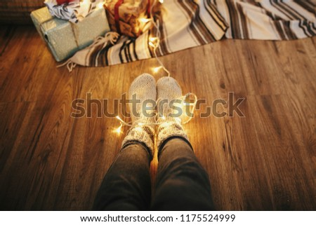 girl legs in stylish warm sock sitting with garland lights at christmas tree with gifts. socks on floor  rug in festive room. decor for winter holidays. atmospheric moment