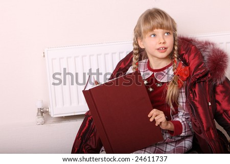 Girl lie near radiator with book. Cold crisis.