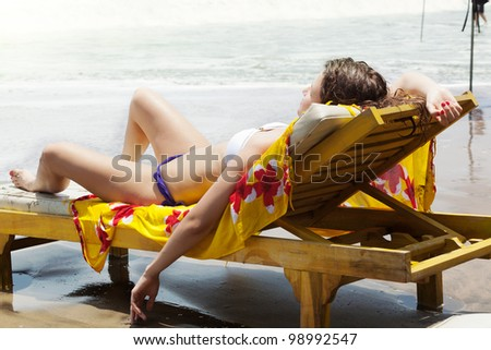 girl lies on a beach plank bed on an ocean coast