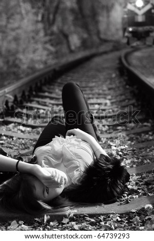 girl lies on rails before train