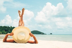 Girl lies on the white sand on the beach. Woman tanning relaxing on beach. Female adult from the back lying down with straw hat sunbathing under the tropical sun