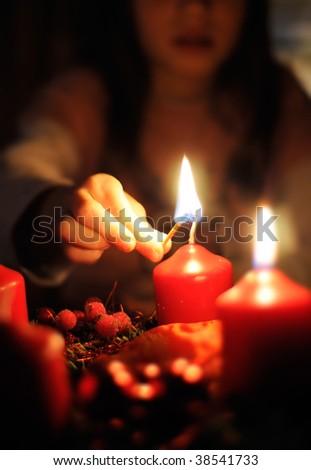 Girl light a Candle on a Christmas Wreath