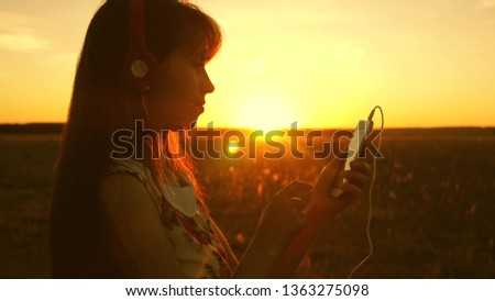 girl listening to music and dancing in the rays of a beautiful sunset. young girl in headphones and with a smartphone touches finger to the sensor of the tablet selects songs online. Slow motion. #1363275098