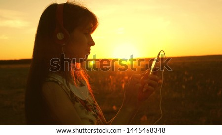 girl listening to music and dancing in the rays of a beautiful sunset. young girl in headphones and with a smartphone touches finger to the sensor of the tablet selects songs online. Slow motion.
