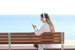 Girl listening to music using smart phone and headphones sititng on a bench on the beach
