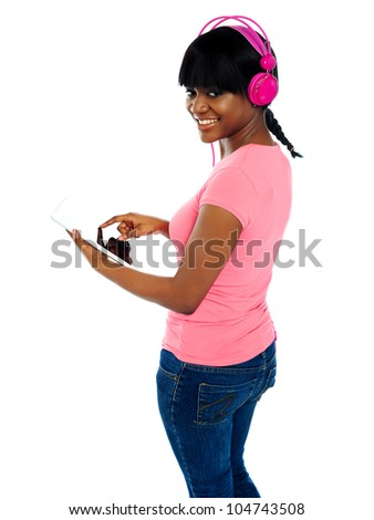 Girl listening to music via portable tablet. Enjoying herself