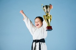 Girl little child in white kimono with belt. Karate fighter child. Karate sport concept. Self defence skills. Karate gives feeling of confidence. Strong and confident small kid. Victory and win.