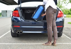 Girl loading a bag into the trunk