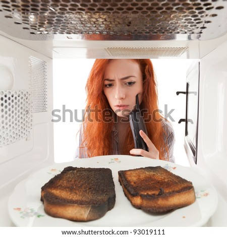 Girl look to a burned toasts in microwave
