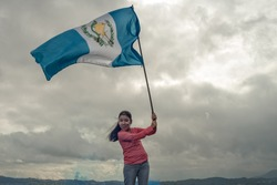 Girl  looking at camera,holding a Guatemala's flag,  with sky background.