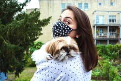 Girl looking at camera wearing a face mask and holding her shihtzu dog