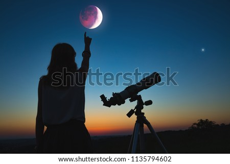Girl looking at lunar eclipse through a telescope. My astronomy work.