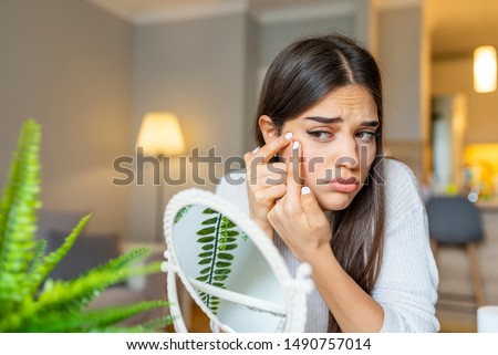 Girl looking at mirror and popping a pimple at home. Girl squeezing pimple at home. Woman examining her face in the mirror, problematic acne-prone skin concept. Upset teenager Foto stock ©