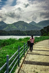 girl looking at pristine lake with mountain background and beautiful hiking trails image is taken at banasura sagar dam wayanad kerala india. the natural beauty of this place is amazing.