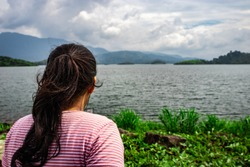 girl looking at pristine lake with mountain background image is taken at banasura sagar dam wayanad kerala india. the natural beauty of this place is amazing.