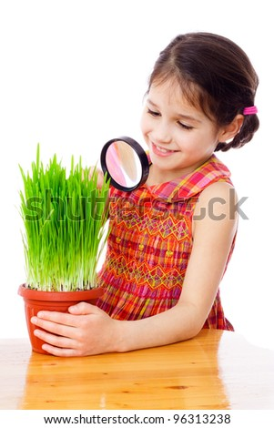 Girl looking at the grass through a magnifying glass on the desk, isolated on white