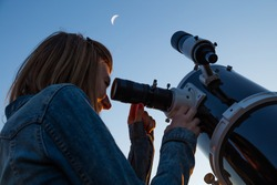 Girl looking at the Moon through a telescope. My astronomy work.