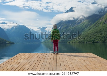 girl looking at the mountains and lake, norway