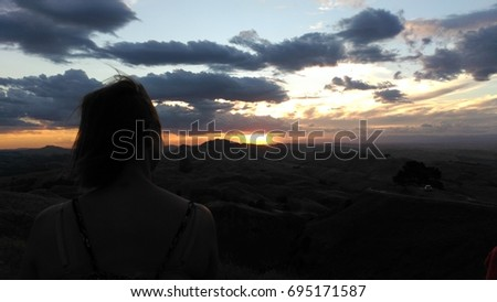 Girl looking at the sunset #695171587