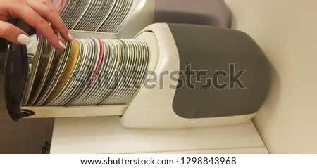 girl looking for music disc in old compact discs plastic box on white shelf #1298843968