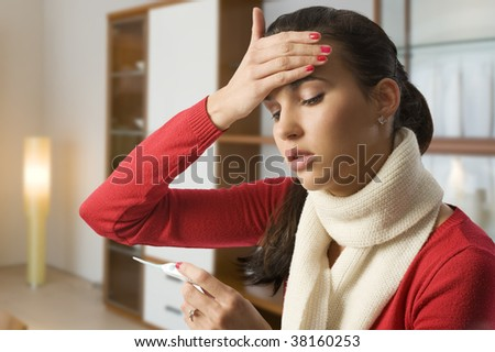 girl looking ill touching her head to check the body temperature