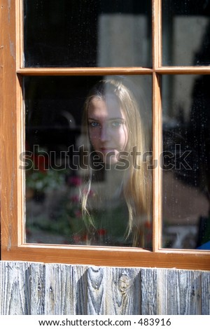 girl looking out a window of an old building