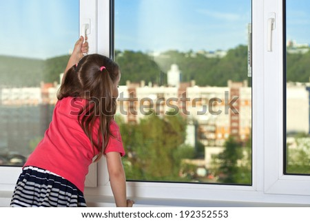 Girl looking out the window, holding the handle on the window frame - stock photo