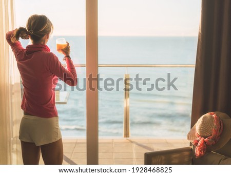 girl looking through a window, just got up and drank a fresh orange juice. She is looking at the Mediterranean sea with a beautiful light. Stockfoto ©