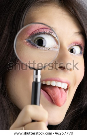 Girl looking through the magnifying glass with tongue hanging out