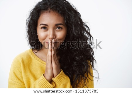Girl looking with tenderness and love as pressing palms together, hold hands in pray grateful, smiling pleased and sincere, very thankful for help, standing white background in yellow sweater