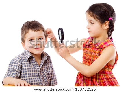 Girl looks at boy's ears through a magnifying glass, isolated on white