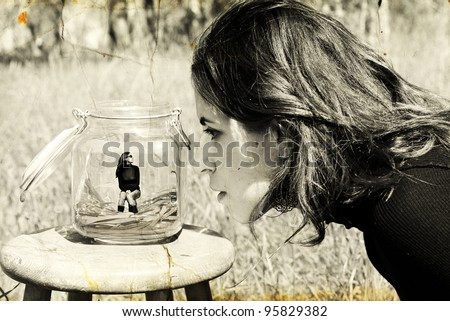 Photo of girl looks at herself in the glass jar. Photo in old image style.