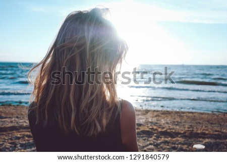 Girl looks on the sea. Dreary blonde girl looks at the sea. Sad for a loved one alone